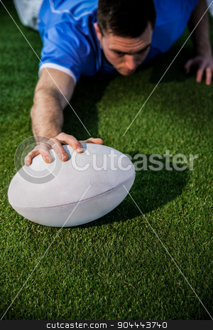 A rugby player scoring a try stock photo, A determined rugby player scoring a try on the grass by Wavebreak Media