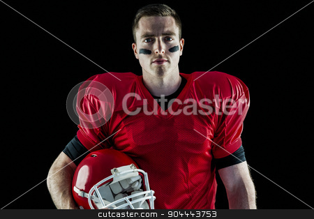 A serious american football player looking at camera stock photo, American football player looking at camera with black background by Wavebreak Media