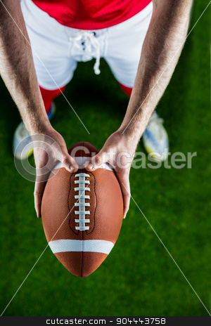 American football player holding up football stock photo, American football player holding up football on american football field by Wavebreak Media