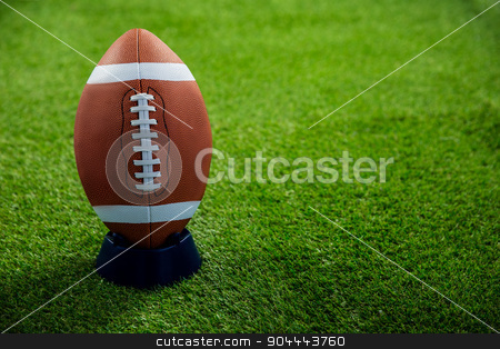 American football standing on holder stock photo, American football standing on holder on american football field by Wavebreak Media