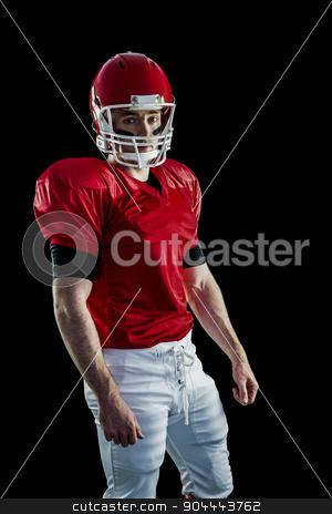 Portrait of american football player wearing his helmet stock photo, Portrait of american football player wearing his helmet against black background by Wavebreak Media