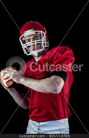 Portrait of american football player being about to throw footba stock photo, Portrait of american football player being about to throw football against black background by Wavebreak Media