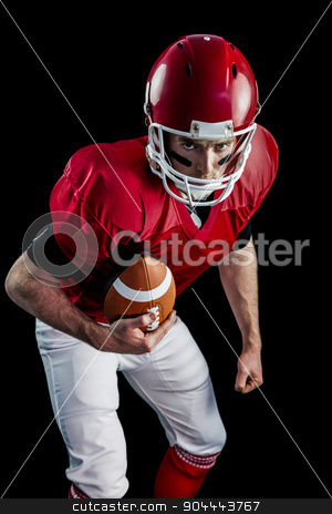 Portrait of focused american football player being ready to atta stock photo, Portrait of focused american football player being ready to attack against black background by Wavebreak Media
