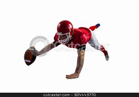 American football player reaching football stock photo, American football player reaching football on american football field by Wavebreak Media