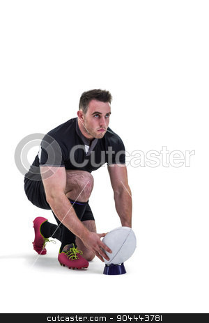 Rugby player getting ready to kick ball stock photo, Rugby player getting ready to kick ball on white background by Wavebreak Media