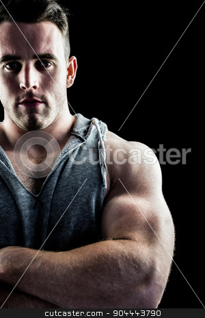 Handsome bodybuilder with arms crossed stock photo, Handsome bodybuilder with arms crossed on black background by Wavebreak Media