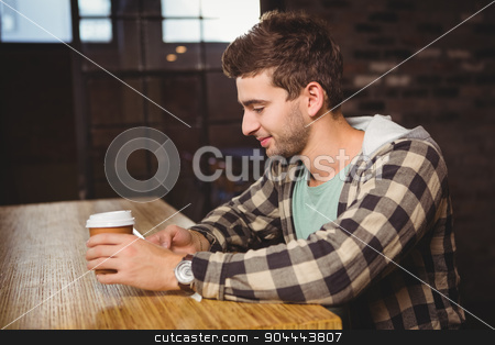 Smiling hipster texting and holding take-away cup stock photo, Smiling hipster texting and holding take-away cup at coffee shop by Wavebreak Media