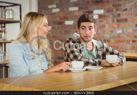 Smiling hipsters sitting and talking stock photo, Smiling hipsters sitting and talking at coffee shop by Wavebreak Media