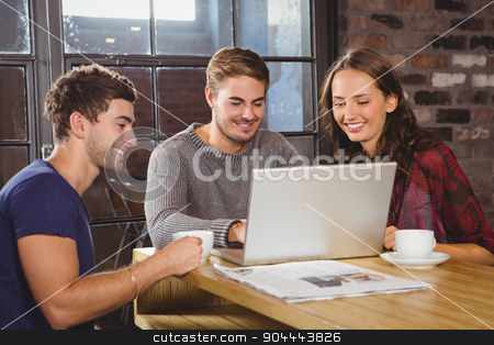 Smiling friends having coffee together and looking at laptop stock photo, Smiling friends having coffee together and looking at laptop at coffee shop by Wavebreak Media