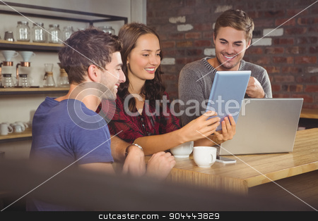 Smiling friends looking at tablet computer stock photo, Smiling friends looking at tablet computer at coffee shop by Wavebreak Media