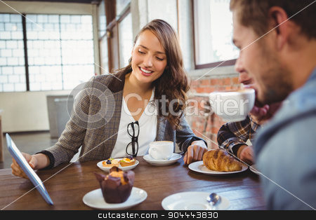 Smiling friends enjoying coffee and looking at tablet stock photo, Smiling friends enjoying coffee and looking at tablet at coffee shop by Wavebreak Media