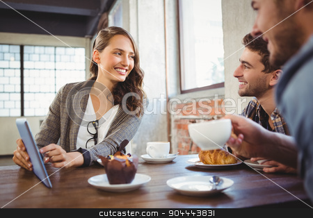 Smiling friends using tablet computer together stock photo, Smiling friends using tablet computer together at coffee shop by Wavebreak Media