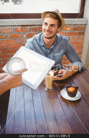 Waitress taking handsome hipsters order with tablet stock photo, Waitress taking handsome hipsters order with tablet at coffee shop by Wavebreak Media