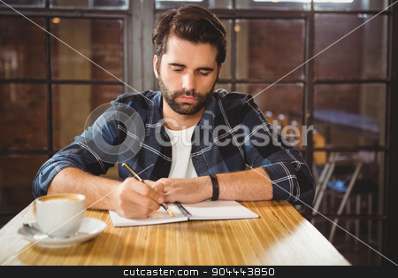 Young man taking notes in his notebook stock photo, Young man taking notes in his notebook at a cafe by Wavebreak Media