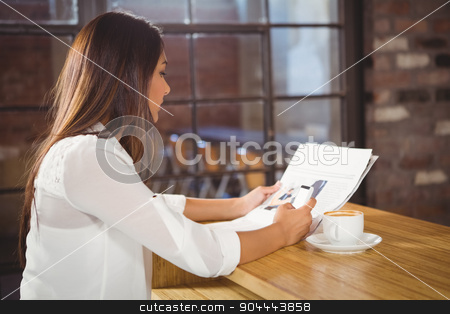 Casual businesswoman looking at files stock photo, Casual businesswoman looking at files in a cafe by Wavebreak Media
