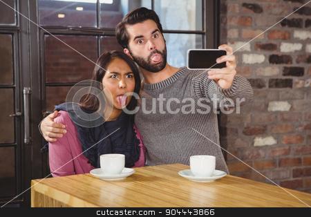 Grimacing friends taking selfies stock photo, Grimacing friends taking selfies at the cafe by Wavebreak Media