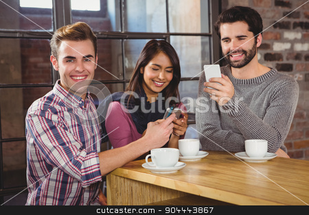 Group of friends looking at their smartphone stock photo, Group of friends looking at their smartphone in a cafe by Wavebreak Media