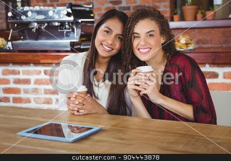 Pretty female friends enjoying a coffee using tablet pc stock photo, Pretty female friends enjoying a coffee using tablet pc at the coffee shop by Wavebreak Media