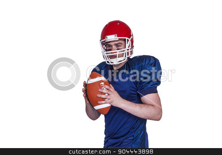 Serious american football player holding a ball stock photo, Serious american football player holding a ball on white background by Wavebreak Media