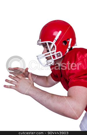 American football player about to catch a ball stock photo, Profile view of an american football player about to catch a ball by Wavebreak Media