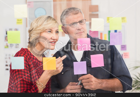 Puzzled business team looking post its on the wall stock photo, Puzzled business team looking post its on the wall in the office by Wavebreak Media