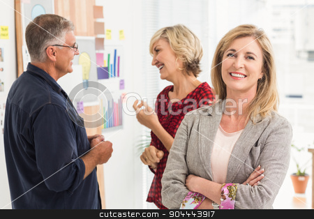 Smiling businesswoman ahead with her team behind stock photo, Smiling businesswoman ahead with her team behind at office by Wavebreak Media