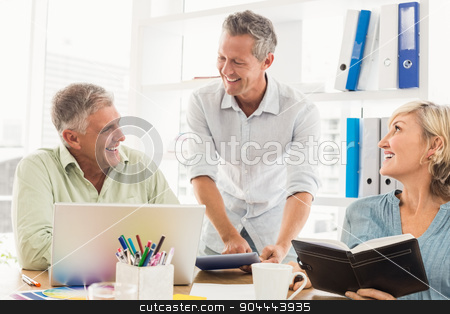 Smiling business team talking in a meeting stock photo, Smiling business team talking in a meeting at the office by Wavebreak Media