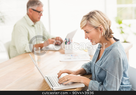 Attentive business team working on laptops stock photo, Attentive business team working on laptops in the office by Wavebreak Media