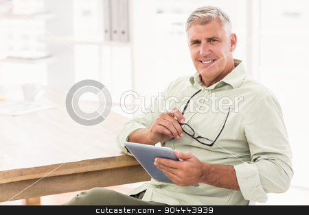 Smiling businessman holding a tablet stock photo, Portrait of a smiling businessman holding a tablet at office by Wavebreak Media