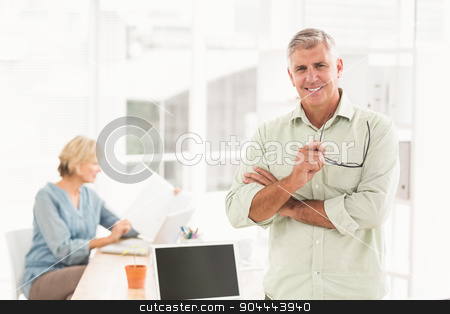 Standing smiling businessman looking at the camera stock photo, Portrait of a standing businessman with arms crossed at the office by Wavebreak Media