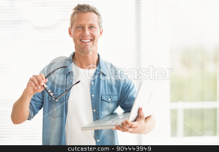 Smiling businessman holding a laptop stock photo, Portrait of a smiling businessman holding a laptop at office by Wavebreak Media