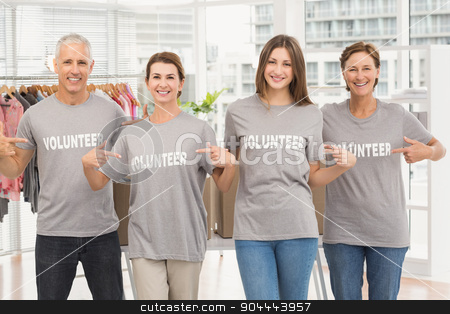Smiling volunteers pointing on their shirts stock photo, Portrait of smiling volunteers pointing on their shirts in the office by Wavebreak Media