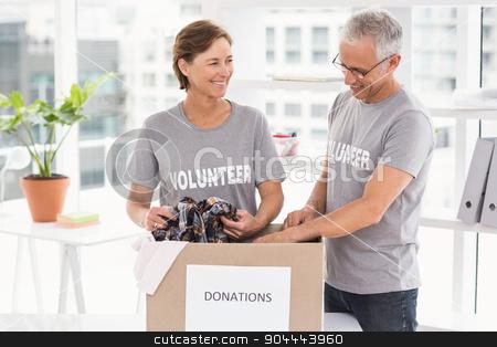 Smiling volunteers sorting donation box stock photo, Smiling volunteers sorting donation box in the office by Wavebreak Media
