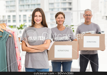 Smiling volunteers holding donation boxes stock photo, Portrait of smiling volunteers holding donation boxes in the office by Wavebreak Media