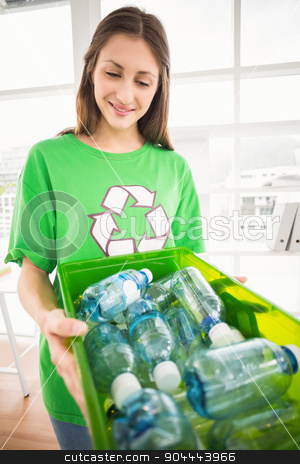 Smiling eco-minded brunette showing recycling box stock photo, Smiling eco-minded brunette showing recycling box in the office by Wavebreak Media