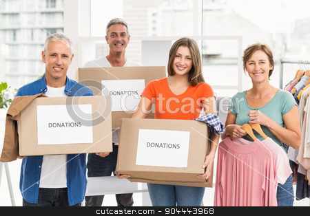 Smiling casual business people with donation boxes stock photo, Portrait of smiling casual business people with donation boxes in the office by Wavebreak Media