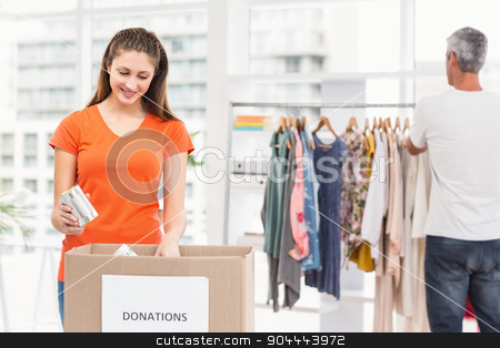 Casual business colleagues sorting donations stock photo, Casual business colleagues sorting donations in the office by Wavebreak Media