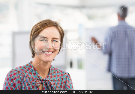 Smiling casual businesswoman in front of colleague stock photo, Smiling casual businesswoman in front of colleague in the office by Wavebreak Media