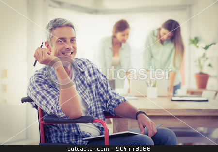 Smiling casual businessman in wheelchair stock photo, Portrait of smiling casual businessman in wheelchair in the office by Wavebreak Media