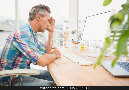 Frustrated casual designer using computer stock photo, Frustrated casual designer using computer in the office by Wavebreak Media
