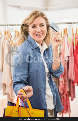 Smiling woman with shopping bags showing credit card stock photo, Portrait of smiling woman with shopping bags showing credit card in clothing store by Wavebreak Media