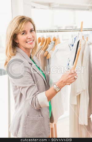 Smiling woman browsing clothes stock photo, Portrait of smiling woman browsing clothes in clothing store by Wavebreak Media