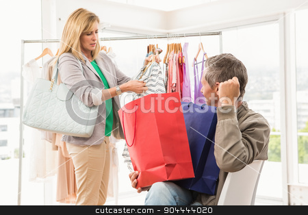 Man sitting and waiting for his shopping woman stock photo, Man sitting and waiting for his shopping woman in clothing store by Wavebreak Media