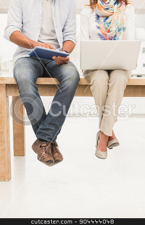 Casual designers sitting on wooden desk and using devices stock photo, Casual designers sitting on wooden desk and using devices in the office by Wavebreak Media