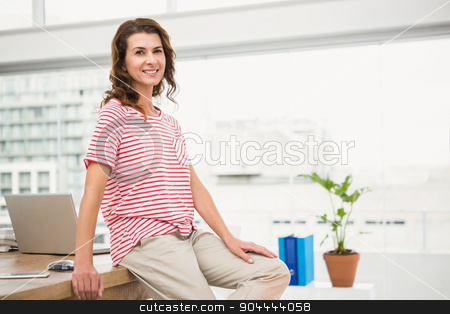 Smiling casual businesswoman leaning on desk stock photo, Portrait of smiling casual businesswoman leaning on desk in the office by Wavebreak Media