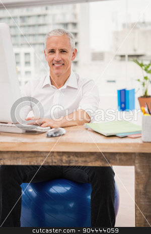 Smiling casual businessman sitting on exercise ball at desk stock photo, Portrait of smiling casual businessman sitting on exercise ball at desk in the office by Wavebreak Media