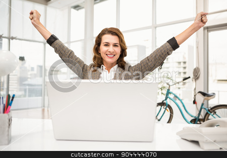 Smiling casual businesswoman celebrating success stock photo, Portrait of smiling casual businesswoman celebrating success in the office by Wavebreak Media
