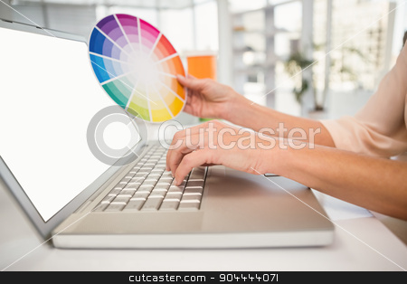 Casual designer working with laptop and colour chart stock photo, Casual designer working with laptop and colour chart in the office by Wavebreak Media