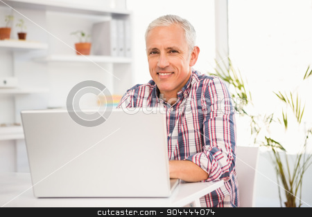 Smiling casual businessman working with computer stock photo, Portrait of smiling casual businessman working with computer in the office by Wavebreak Media