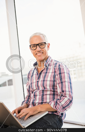Smiling casual businessman using laptop stock photo, Portrait of smiling casual businessman using laptop in the office by Wavebreak Media